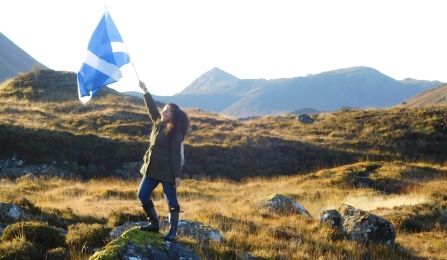 UB Law student standing on a rock holding a flag with mountains in the background in Scotland.