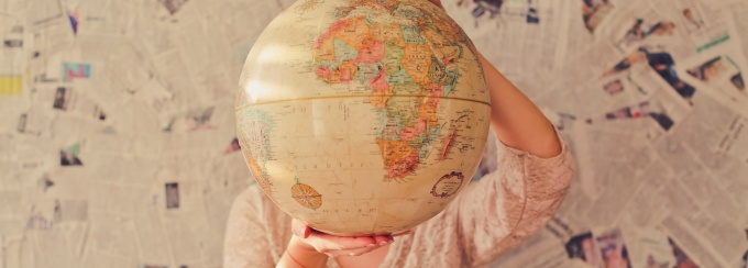 Photo of a person holding a globe in front of their face.