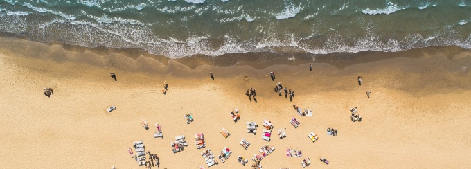 birds eye view of people sitting on a beach.