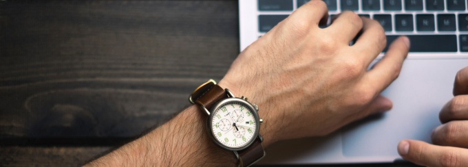person wearing brown and white watch with hand hovering over a laptop