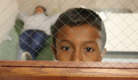 A boy looks out the door window from the room he is staying in at the Brownsville, Texas, port of entry. Photo by Edwardo Perez, courtesy of U.S. Customs and Border Protection.
